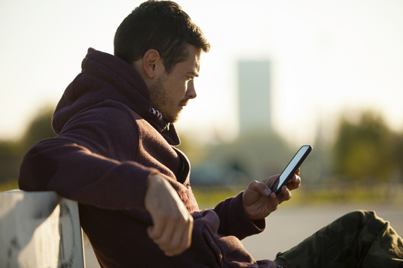Handsome Man In Hoodie Holding and Looking At Mobile Smart Phone Outdoors - How to know if an Aquarius man doesn't like you