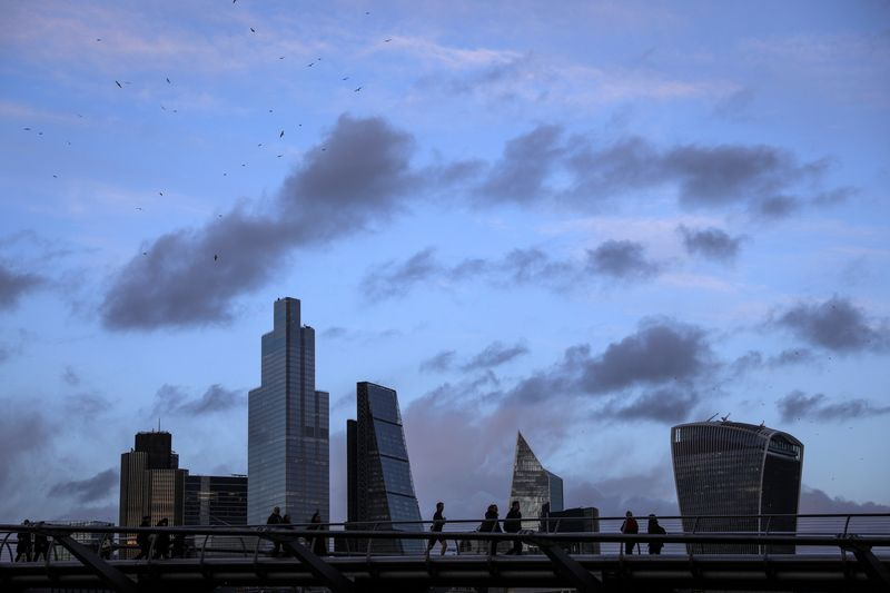 © Reuters. FILE PHOTO: Pedestrians walk over the Millennium Bridge in view of skyscrapers in the financial district in London