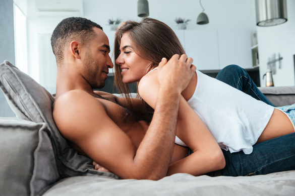 Tender young couple lying and hugging on couch at home - how to show your love to a scorpio man
